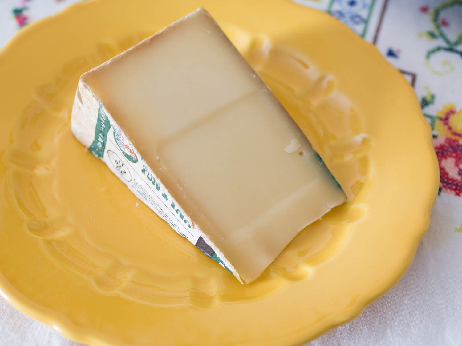 A wedge of fontina val d'aosta cheese on a yellow plate.