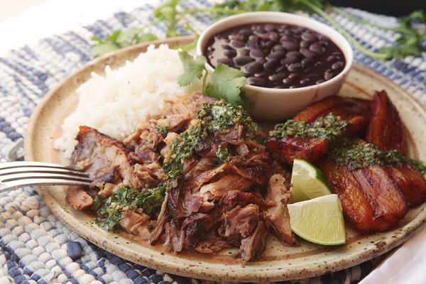 Cuban-style roast pork shoulder with mojo on a plate with white rice, black beans, plantains and lime wedges