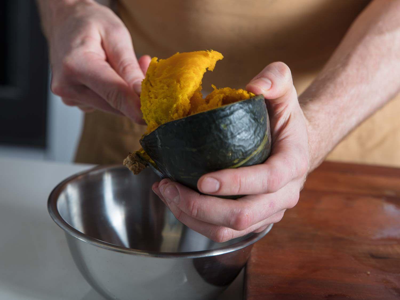 Scooping roasted kabocha squash flesh from skin.