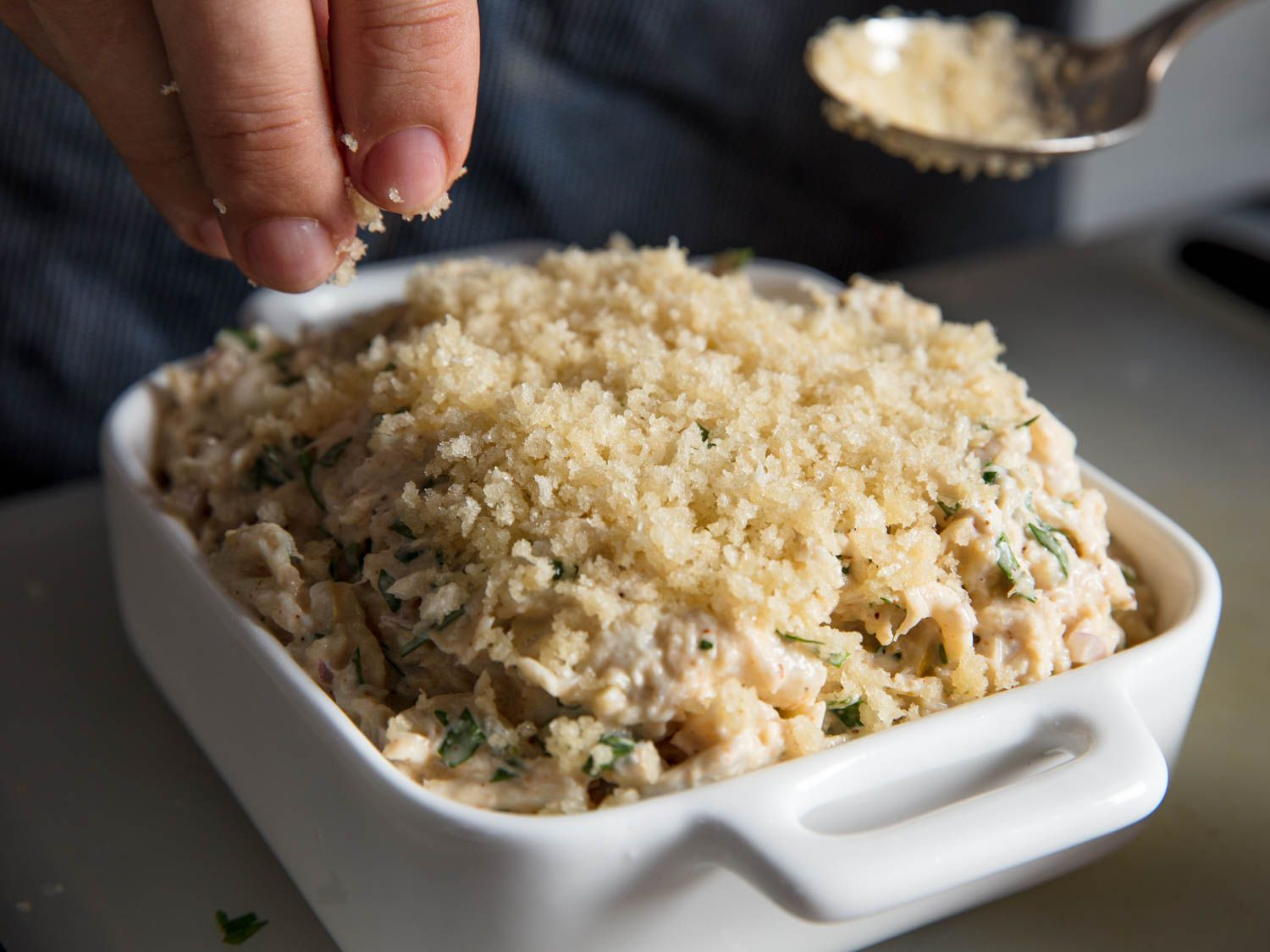 Adding buttered bread crumbs as a topping to a white ceramic baking dish of crab imperial