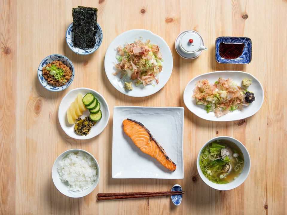 Overhead shot of Japanese breakfast: rice, pickle plate, natto, nori, tofu, soy sauce decanter, soy sauce, eggplant, miso soup, salted salmon on wooden table.