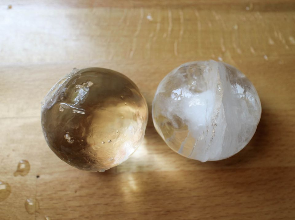 A clear sphere of ice to the left of a cloudy sphere of ice.