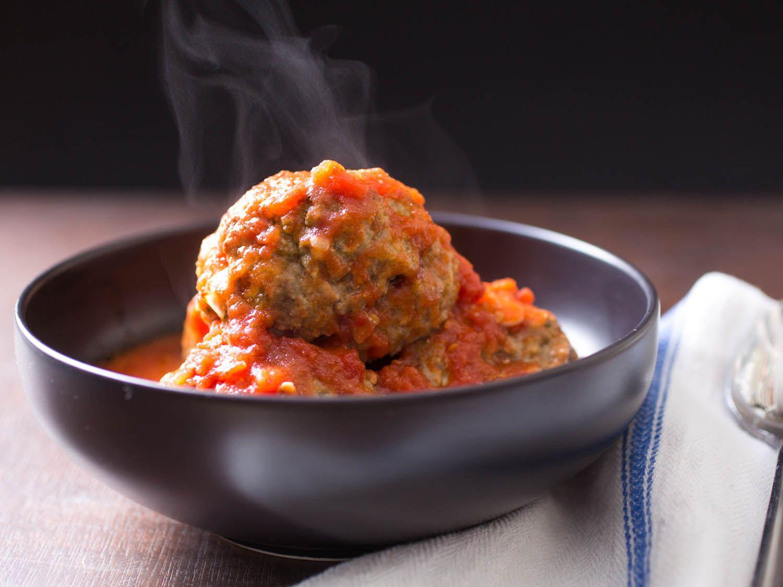 Italian-American meatballs in red sauce in a dark bowl.