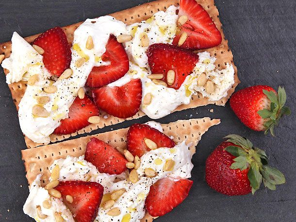 Two pieces of matzo topped with burrata, sliced strawberries, and pine nuts, next to two whole strawberries