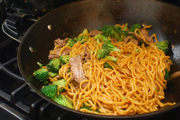 Lo mein with beef and broccoli cooking in a wok on a stovetop.