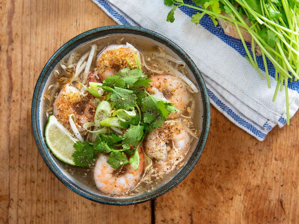 Overhead shot of kuy teav phnom penh (Cambodian soup with rice noodles), with poached shrimp, cilantro leaves, lime wedge, scallions, and bean sprouts