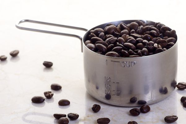 Coffee beans in cup measure.