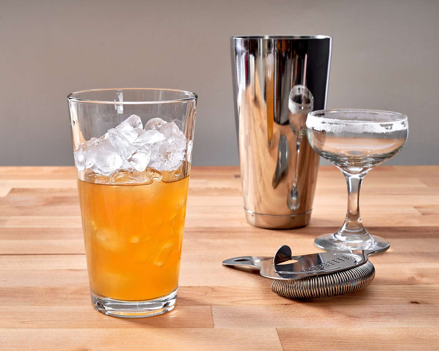 a cocktail shaker glass filled with ingredients for a sidecar cocktail
