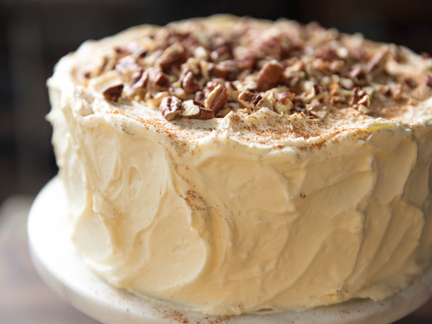 Close-up of finished pumpkin layer cake, frosted with cream cheese buttercream and topped with pecans and cinnamon