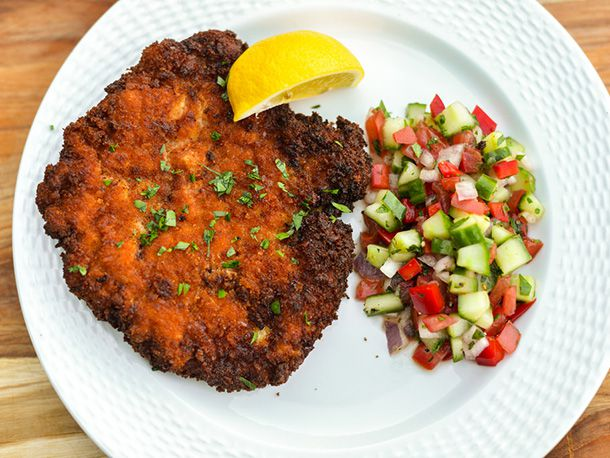 Chicken schnitzel on a white plate with a lemon wedge and a serving of tomato cucumber salad.