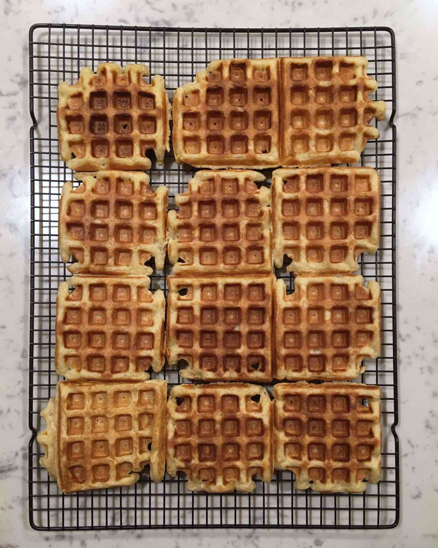 overhead view of 12 waffles made from sourdough starter on a cooling rack