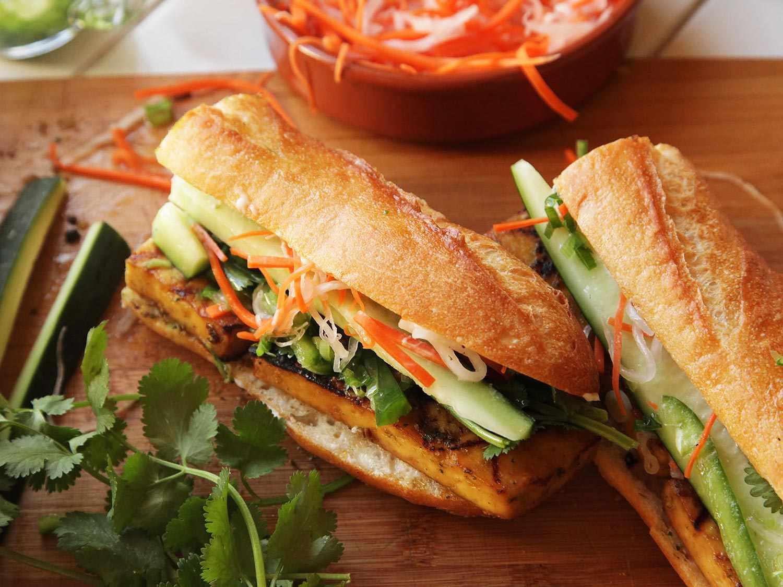 Vegan tofu banh mi sandwiches on a wooden cutting board.