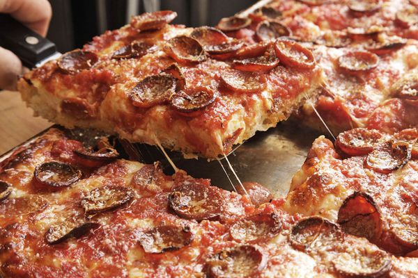 Removing a slice of pepperoni-topped Sicilian pizza from sheet pan.