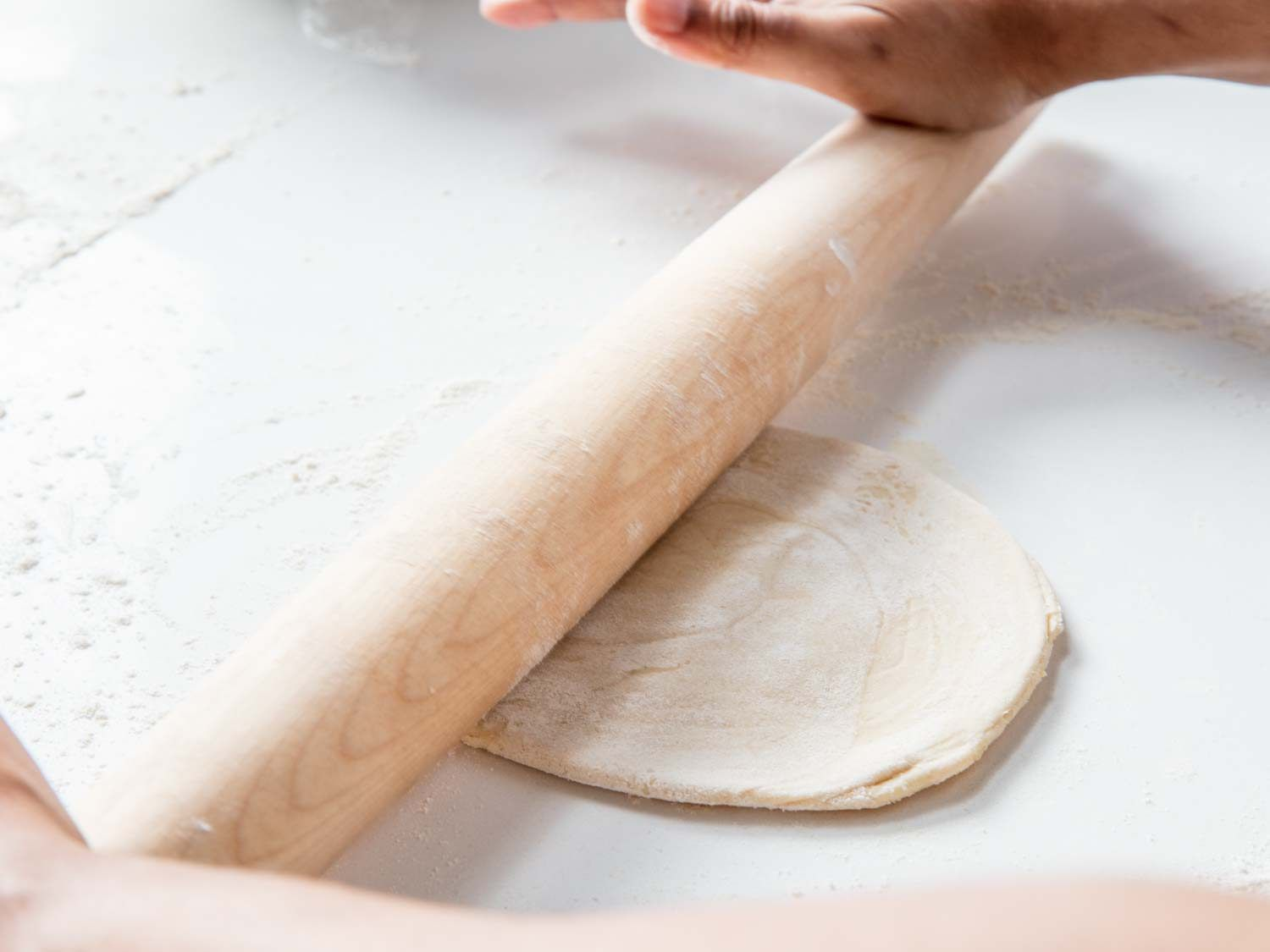 Rolling out paratha dough with a rolling pin