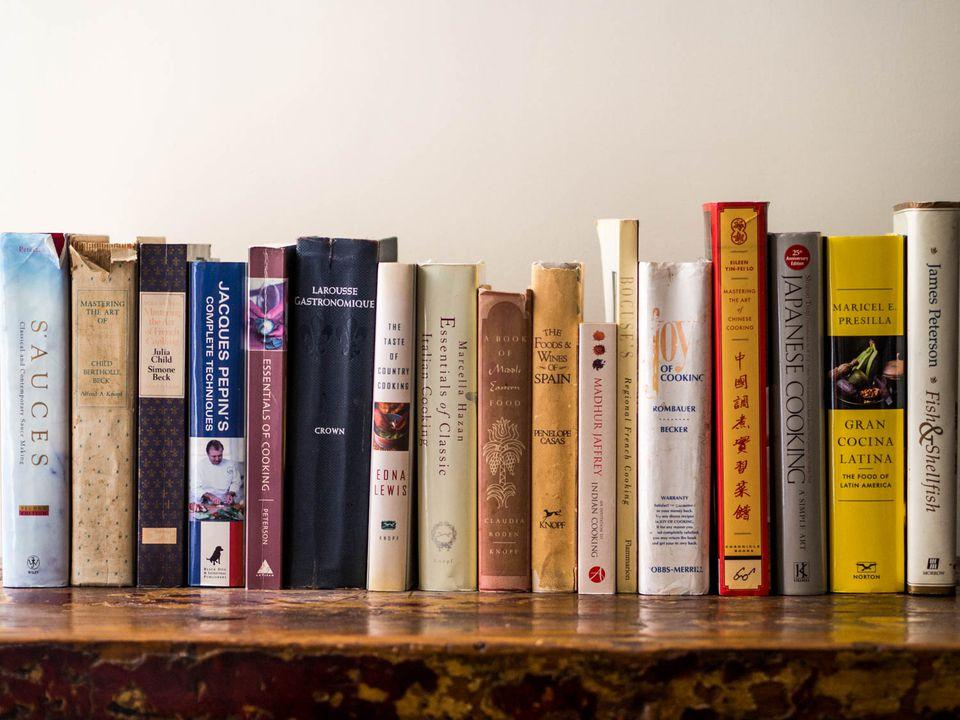 A wooden shelf full of essential cookbooks