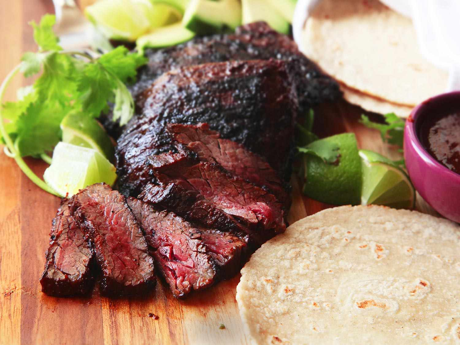 Sliced carne asada surrounded by accoutrements (tortillas, lime wedges, cilantro, and salsa)