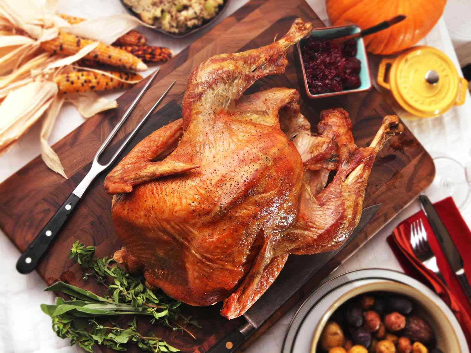 A whole roast turkey on a wooden board, next to a bunch of multicolored corn, a dish of potatoes, and other Thanksgiving accoutrements