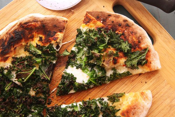 Kale pizza on a cutting board.