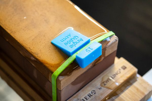 A small plastic 15-degree angle guide is rubber banded to the end of a whetstone