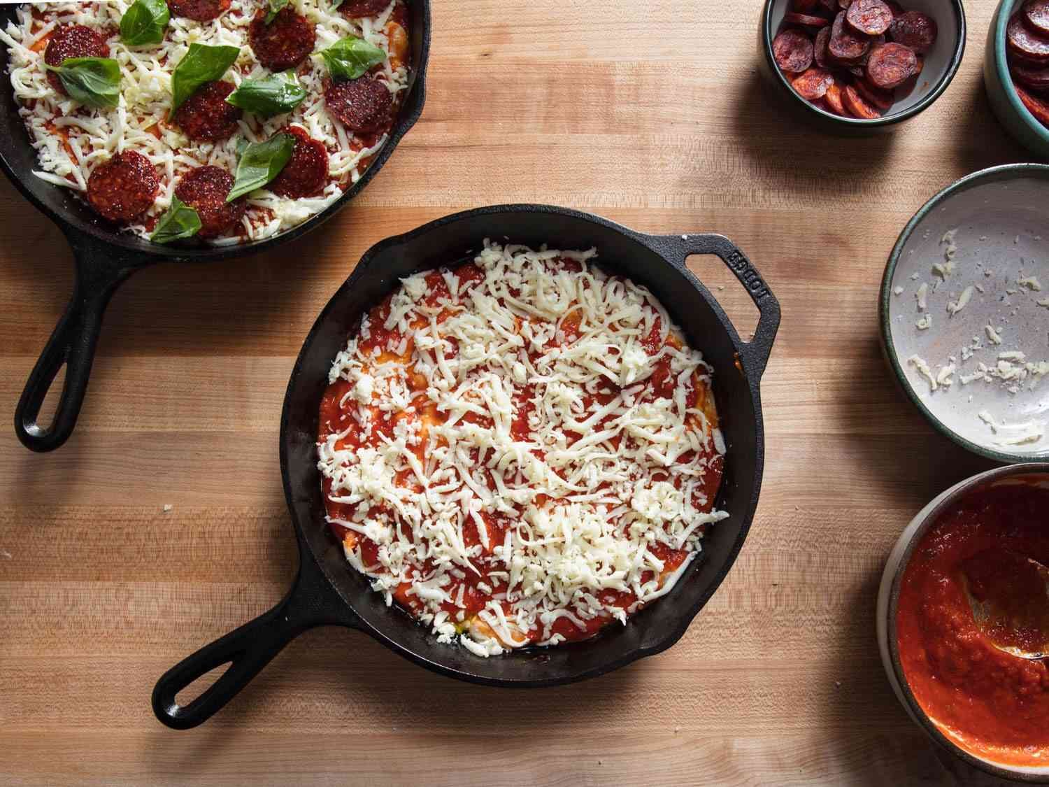 Overhead view of unbaked pan pizza with cheese and toppings