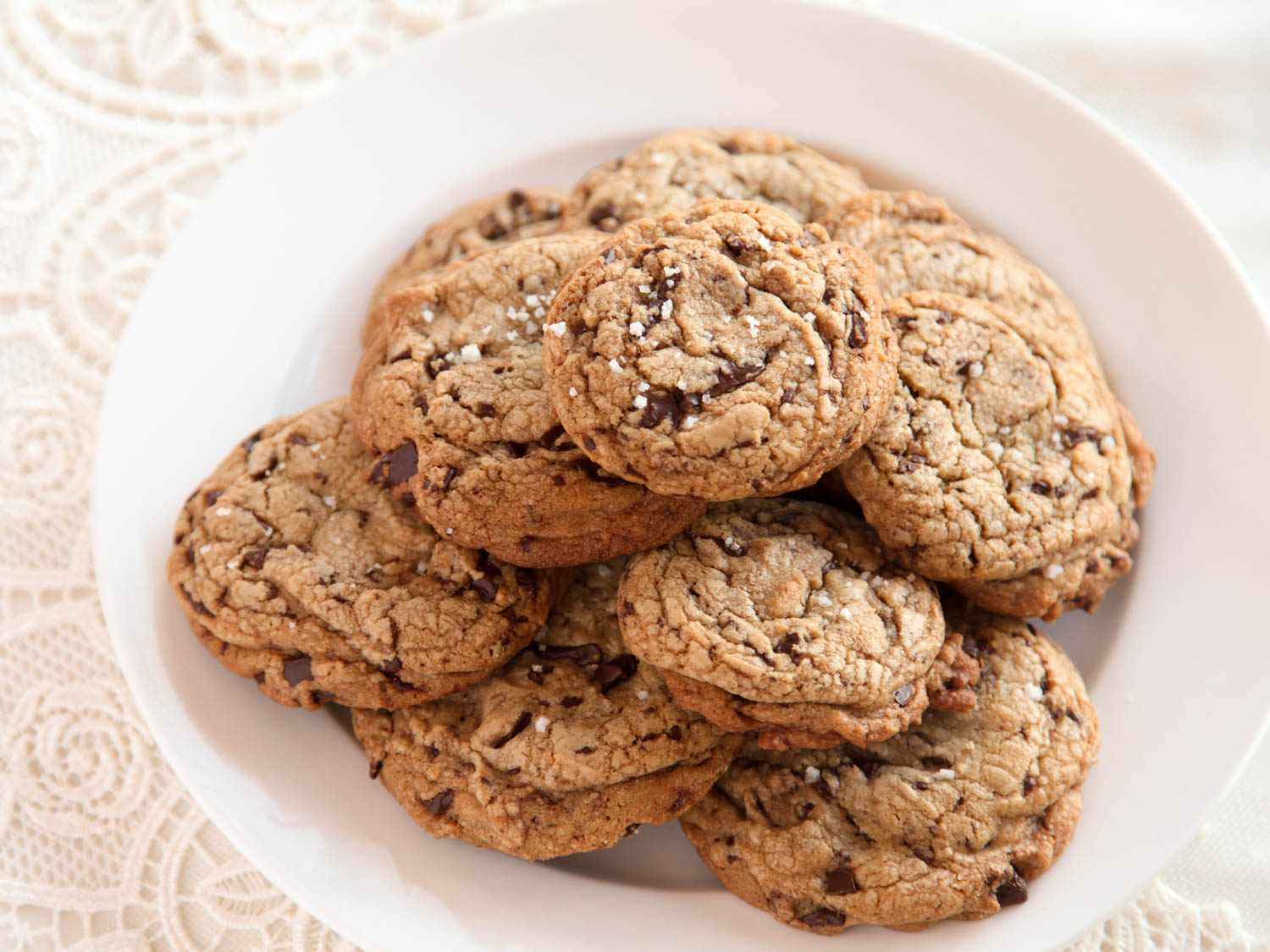 A pile of salted chocolate chip cookies on a white plate, sitting on a lace background.