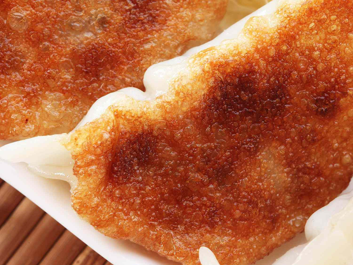 A close up of the bottom of a twice-fried and steamed dumpling. The dumpling is golden brown with lots of crisp texture.