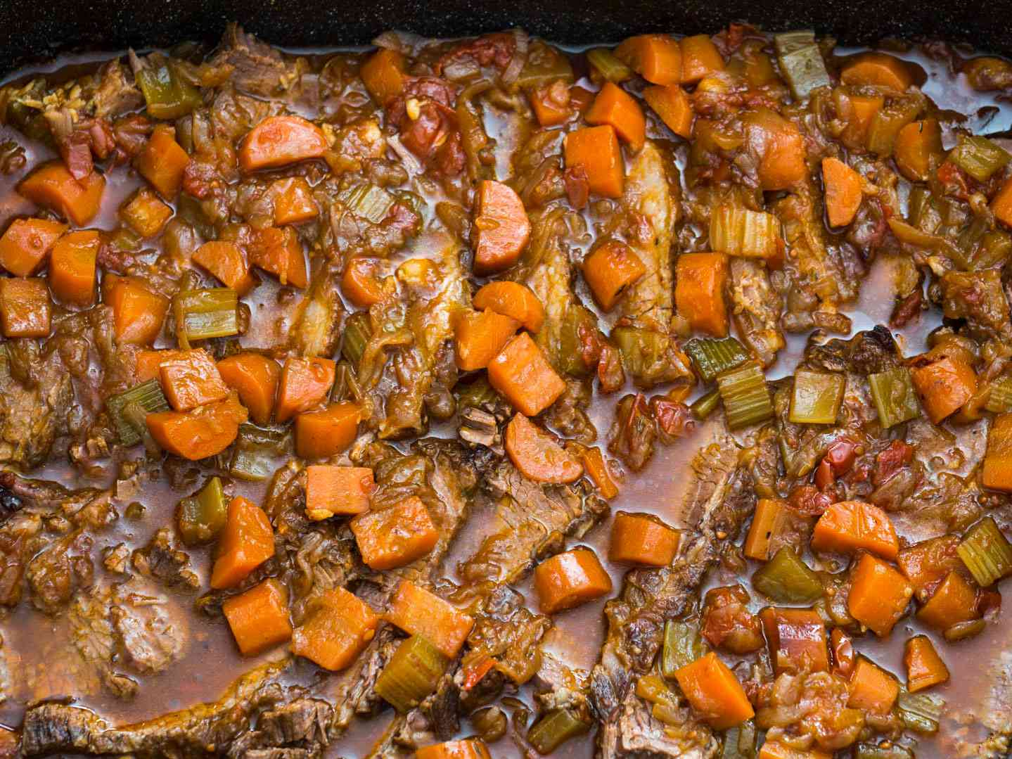 Overhead shot of Jewish-style braised brisket in a sauce with carrots, onions, and other aromatics