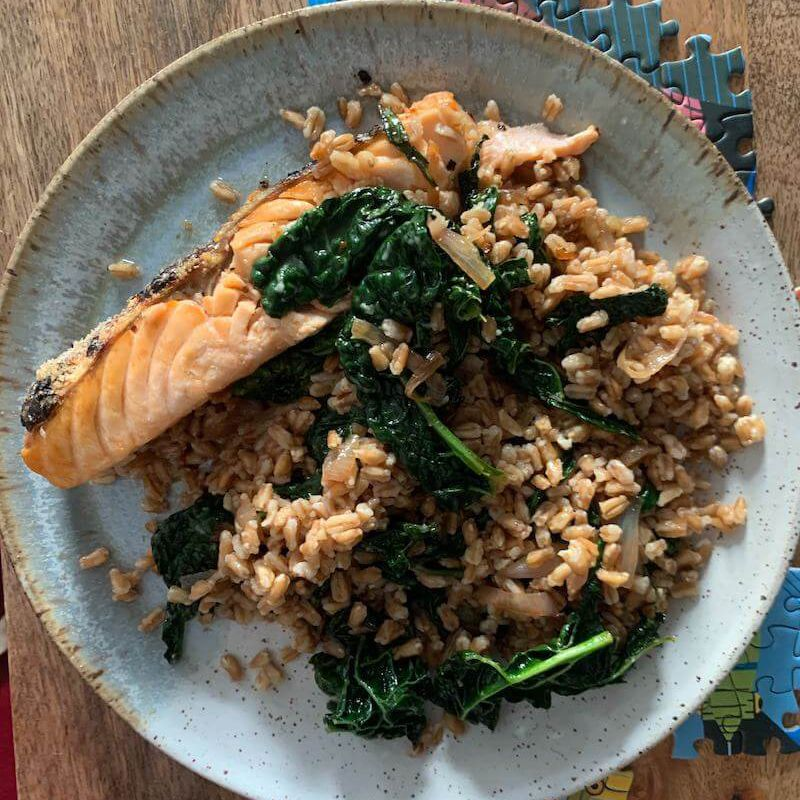 Overhead view of plate of farro and salmon on top of disparate puzzle pieces