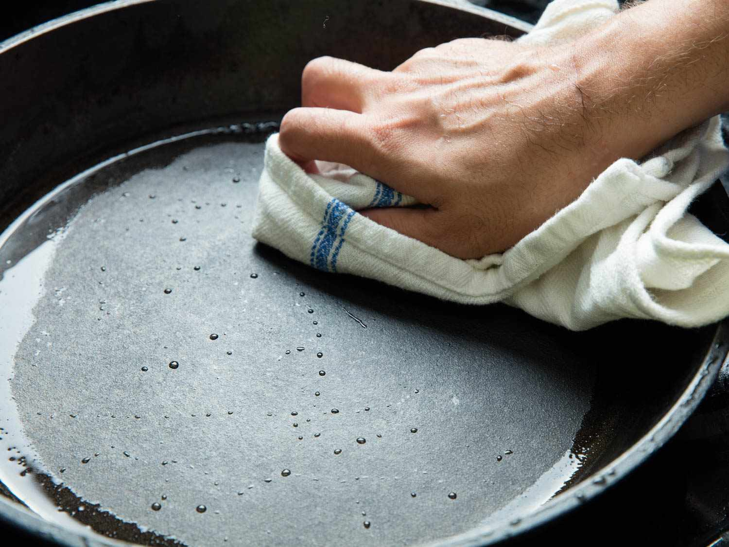 Drying a cast iron pan thoroughly after washing.