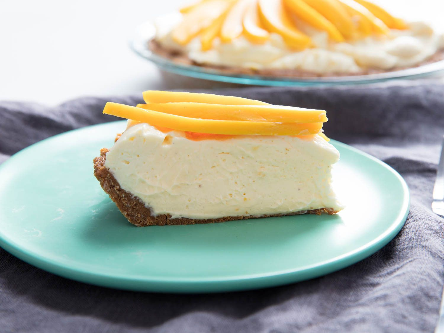 slice of cheesecake with mango slices on top