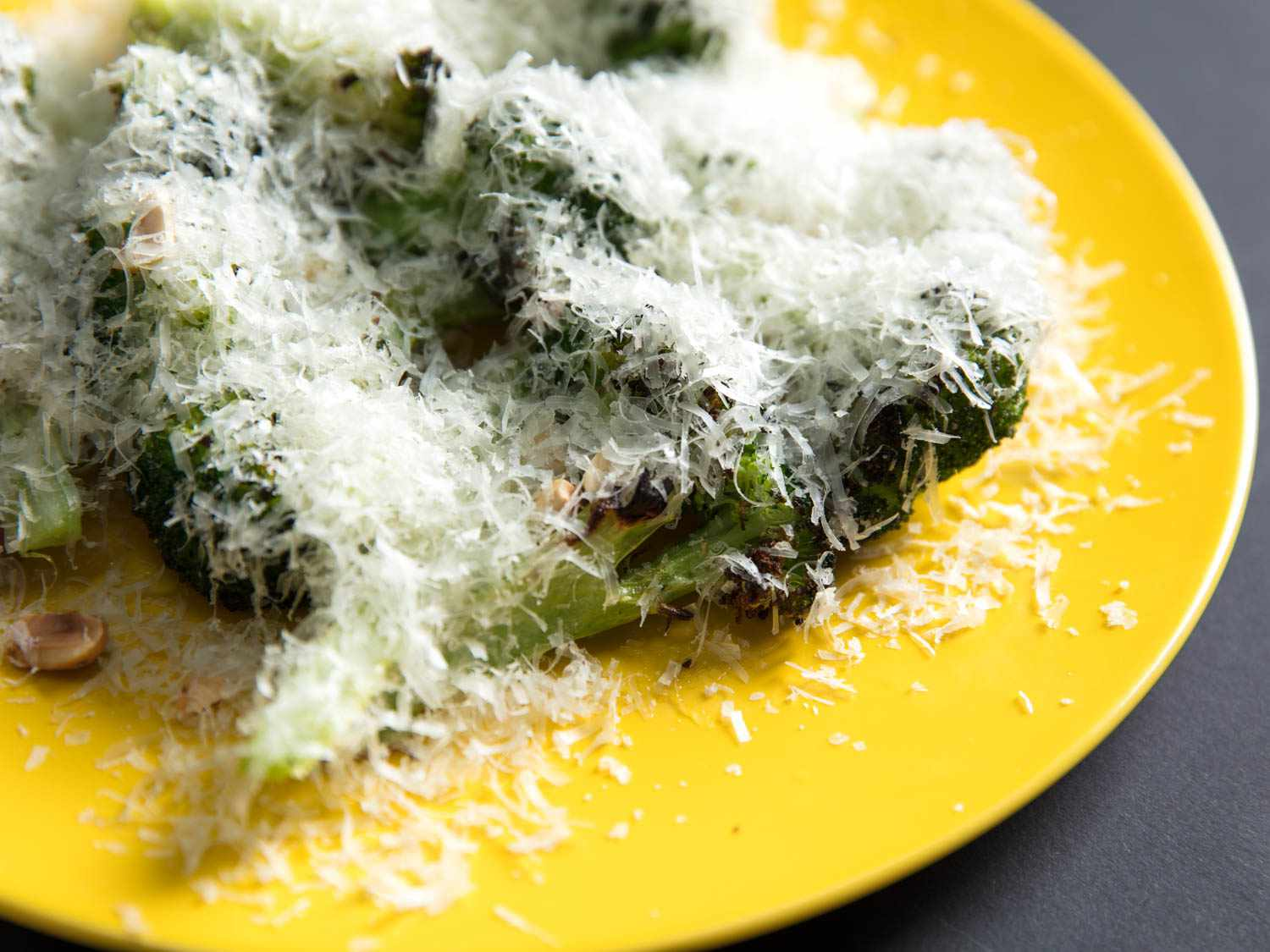 Close-up of charred broccoli with grated Manchego and hazelnuts on a yellow plate