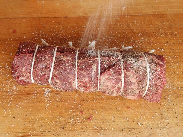Seasoning a tied beef tenderloin with salt and pepper for beef Wellington.