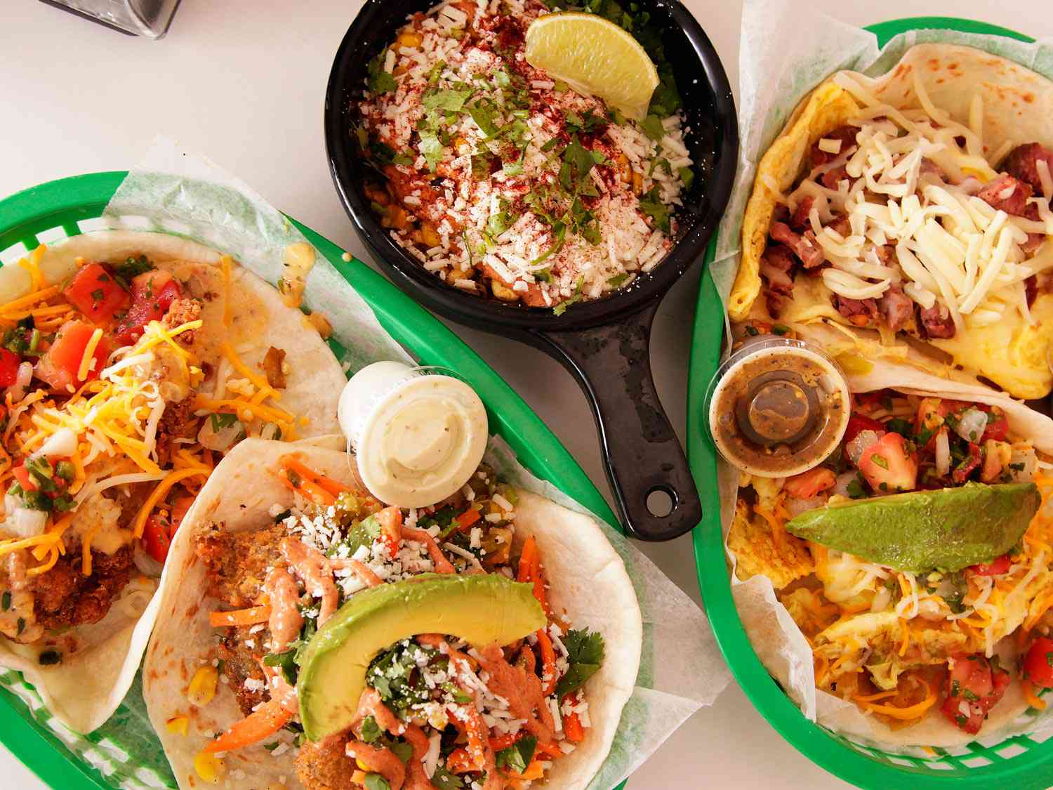 Trays of tacos and a small pan of esquites from Torchy's Tacos