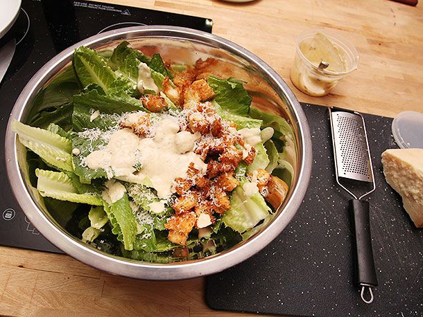 Romaine lettuce leaves, croutons, and Parmesan in a bowl, next to a Microplane grater and a hunk of Parmesan