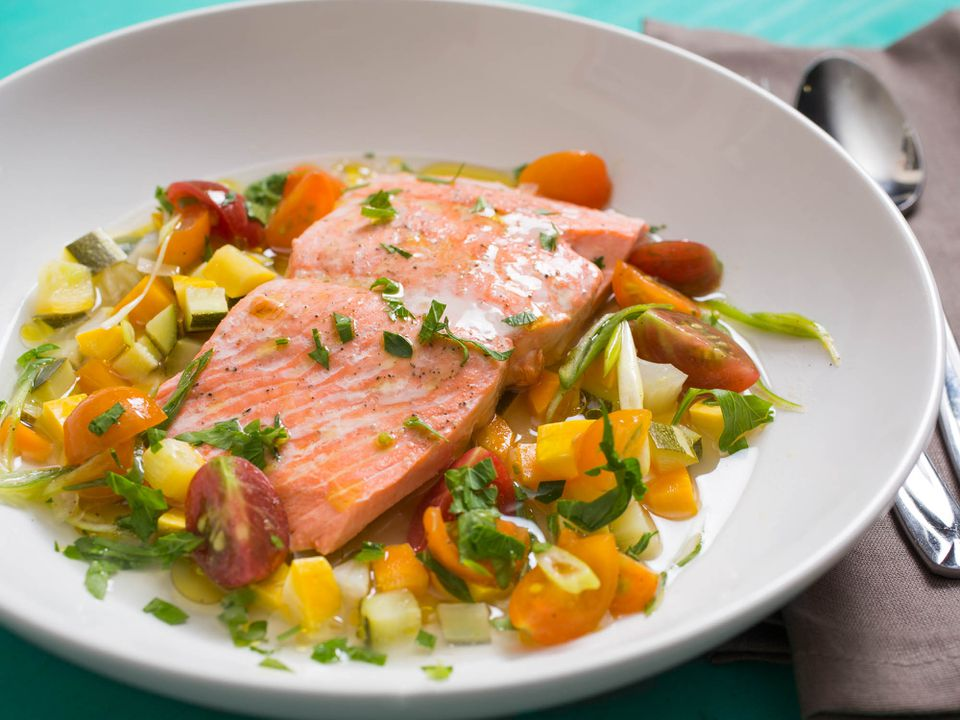 Salmon à la nage with summer vegetables in a white shallow bowl.