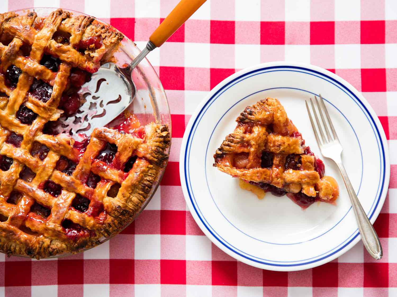 A cherry pie with a piece of cherry pie on a white plate with a fork.