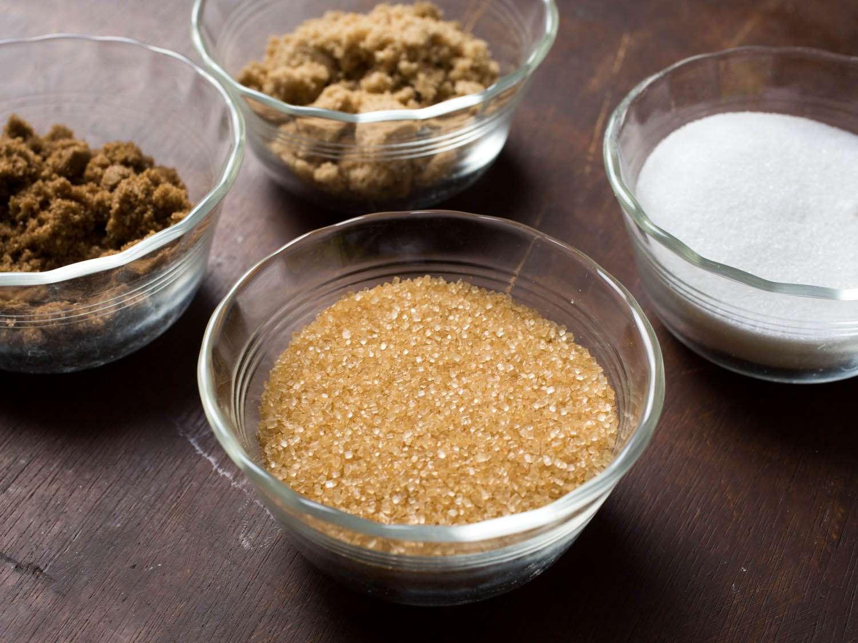 Glass bowls of various types of sugar (raw sugar, white sugar, light brown sugar, and dark brown sugar)