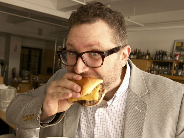 person eating cheeseburger with egg
