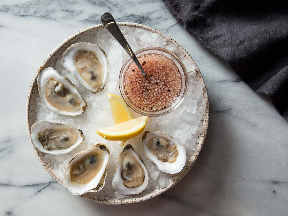 Overhead shot of bowl of oysters with mignonette and lemon wedges