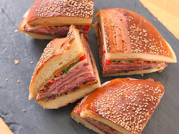 Muffaleta sandwich sliced into quarters, showing cold cuts, and plated on a slate board.