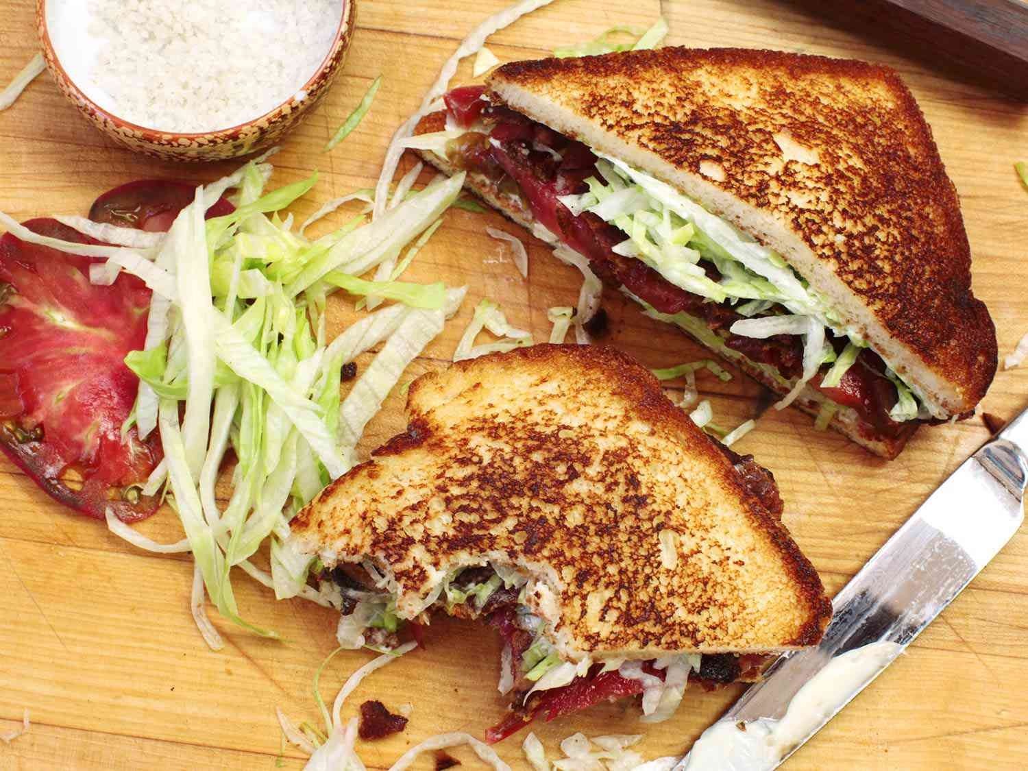 A BLT sandwich cut in half diagonally, one half with bites taken out, with a pile of shredded lettuce and a tomato slice nearby