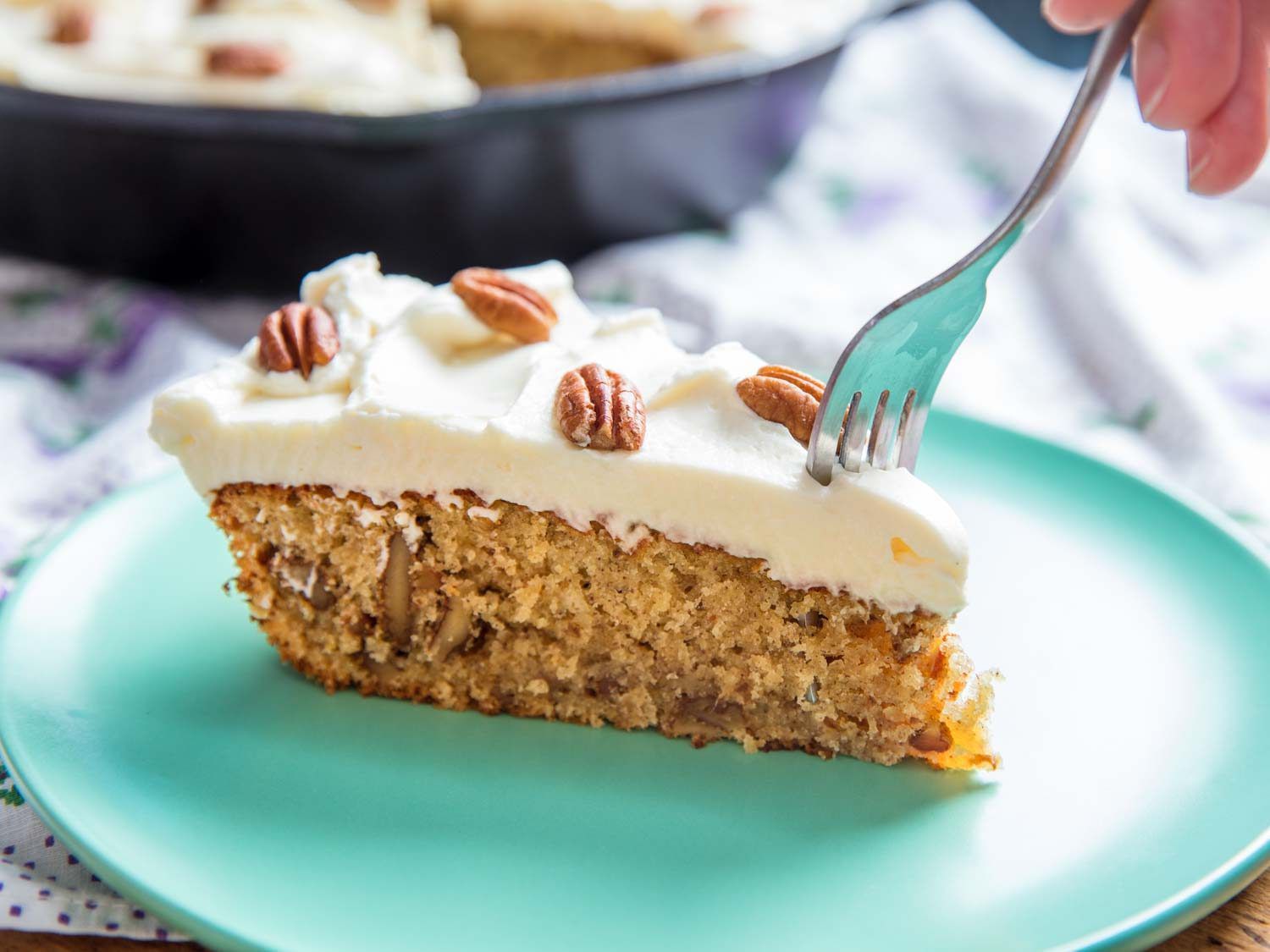Fork digging into skillet hummingbird cake with cream cheese frosting.