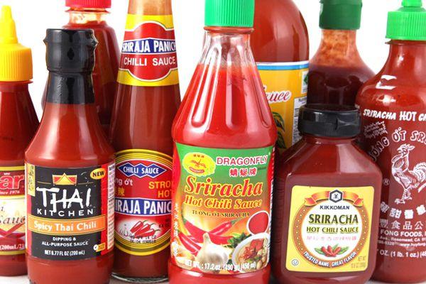 Assorted bottles of different brands of sriracha.