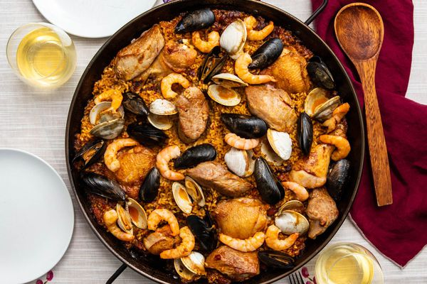 A pan of grilled paella mixta on a table, with mussels, shrimp, chicken, and clams.