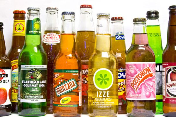 Collection of bottles of apple soda in front of a white background.