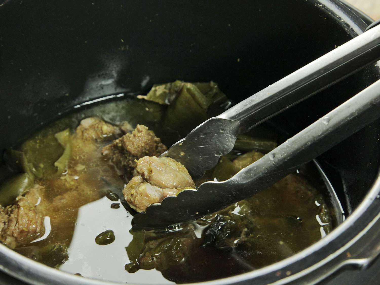 Tongs removing the pork from pressure cooker chile verde stew.