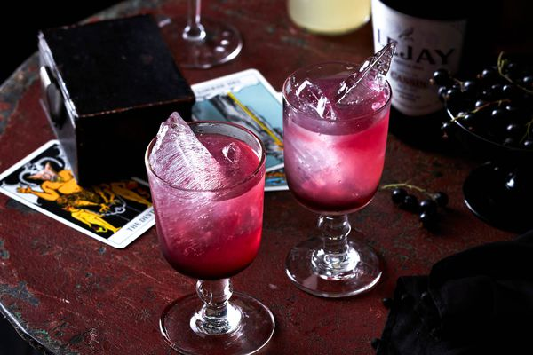 Two glasses of Crème de Cassis on a dark wood table