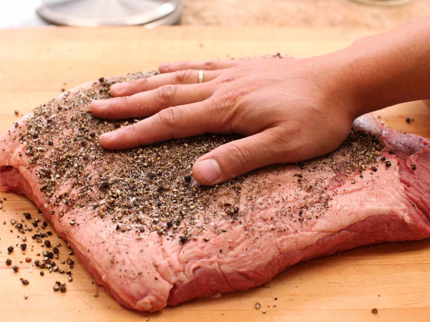 A hand rubbing coarsely ground peppercorns over a slab of brisket
