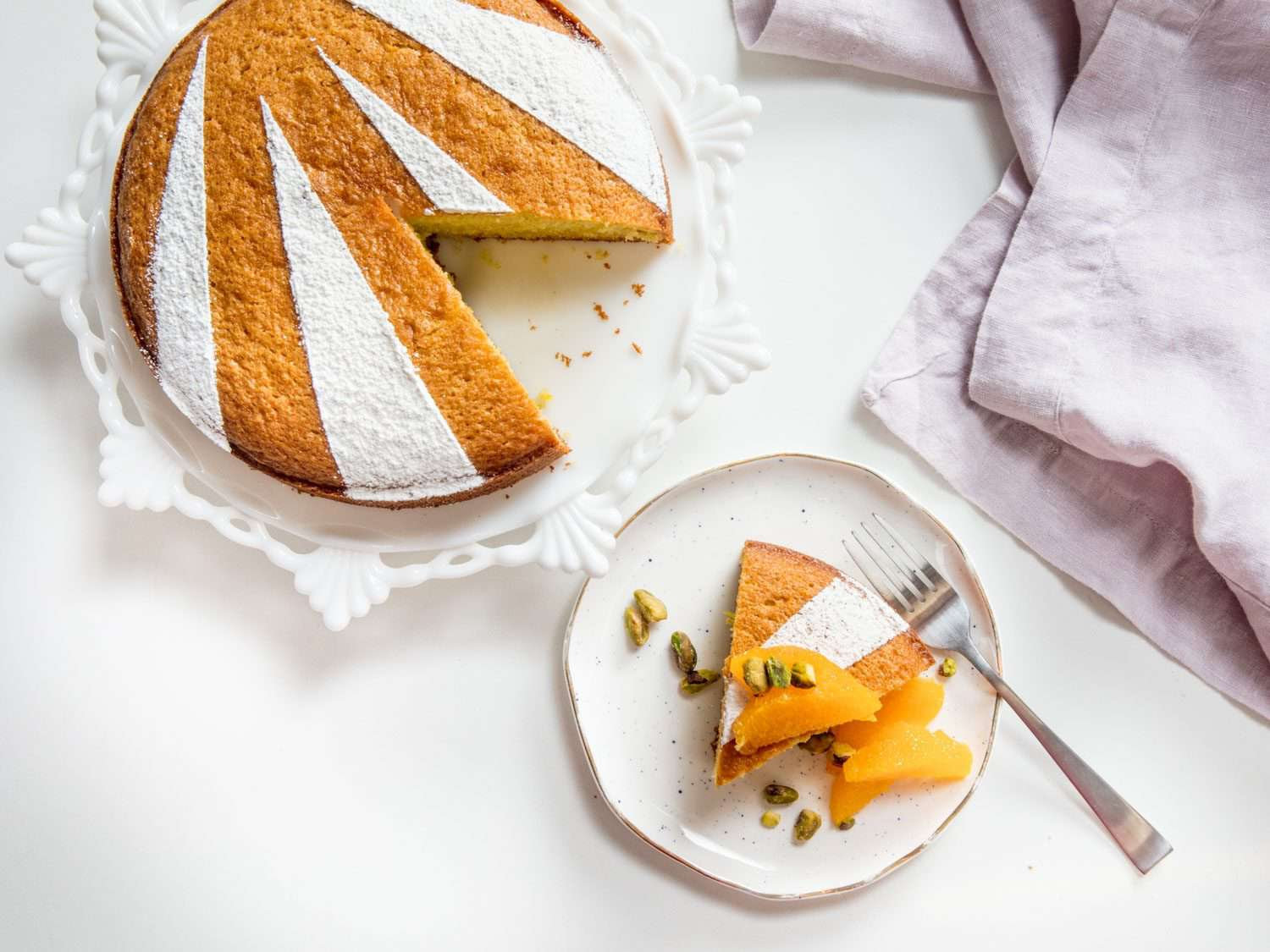 Overhead shot of a slice of olive oil cake on a plate, topped with fruit and nuts, next to the rest of the cake on a cake stand