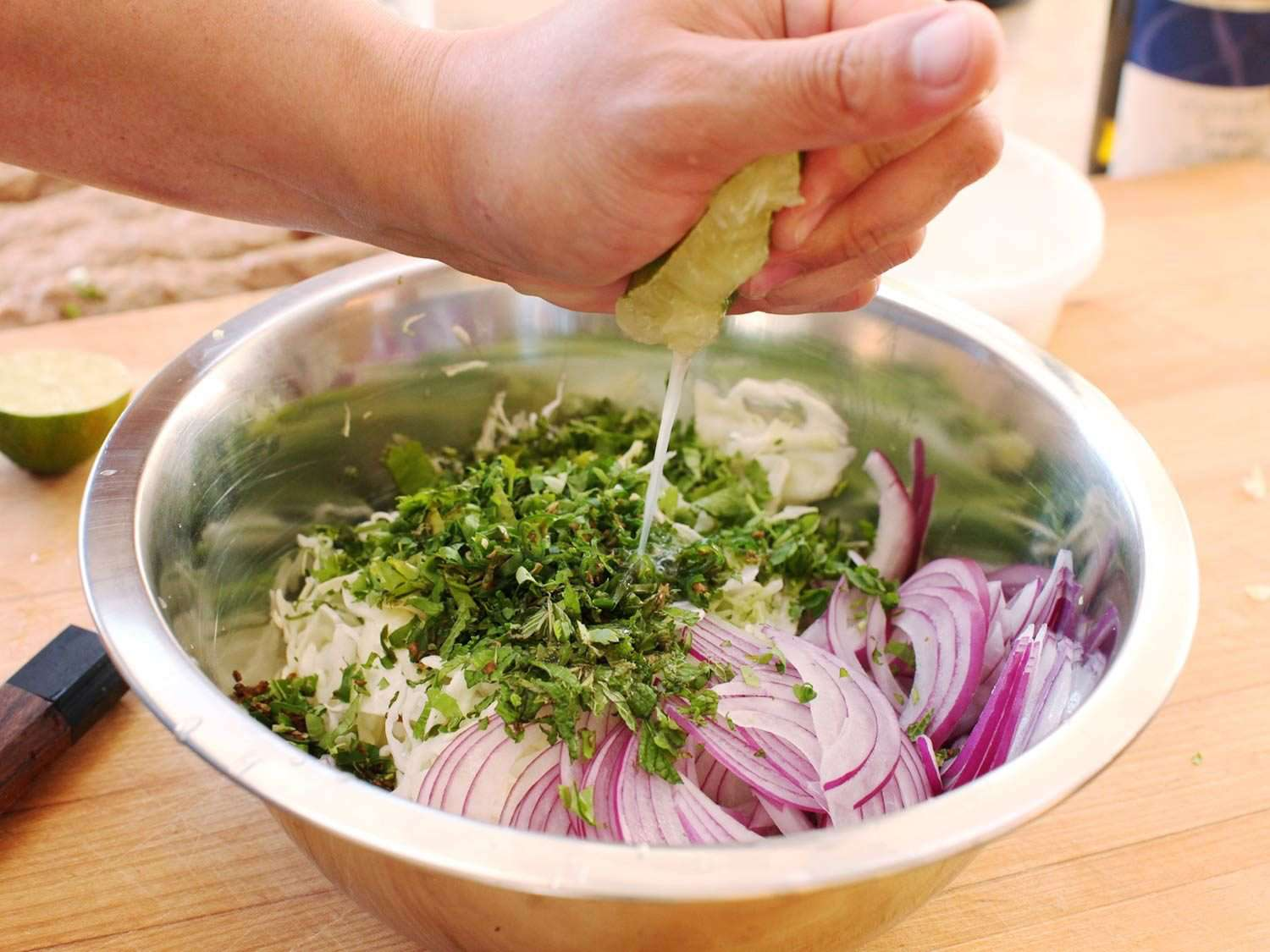 A hand squeezing lime over a metal bowl of cabbage, red onion, and herbs (Spicy Cabbage and Red Onion Slaw)